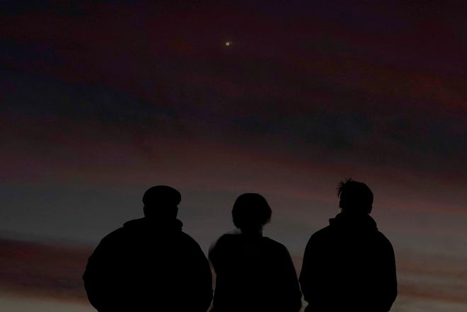 People are shaded in front of the sky at dusk as they watch the alignment of Saturn and Jupiter, Monday, December 21, 2020, in Edgerton, Cannes.