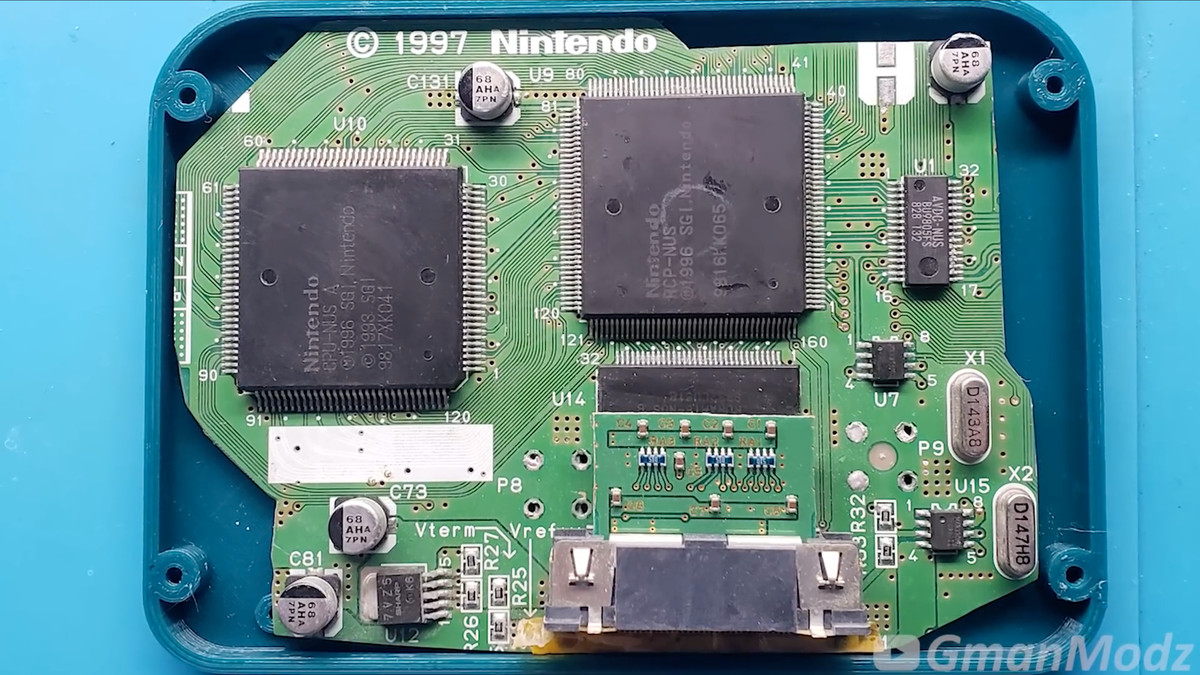 Photo of a Nintendo 64 motherboard seated in a small case.