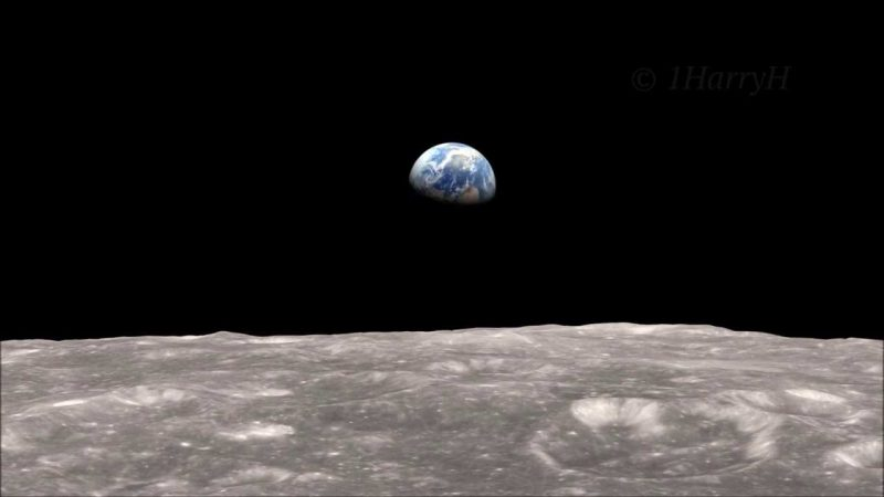 Half of the Earth is floating in the black sky over the moon's gray crater surface.