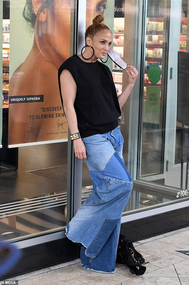 Star power: The Waiting For Tonight singer was pictured taking pictures outside the beauty store where a poster Lopez could be seen in the window promoting JLo Beauty